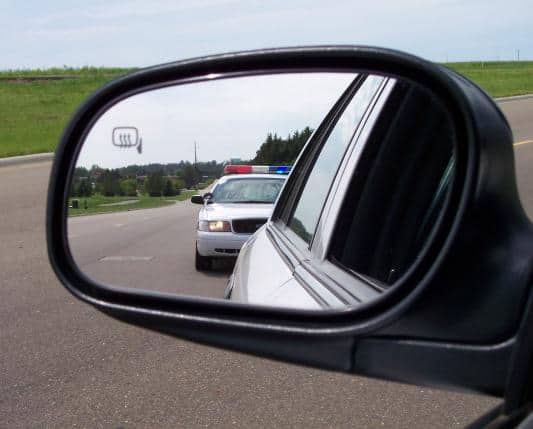 Cop car in rear view mirror in Utah speeding ticket