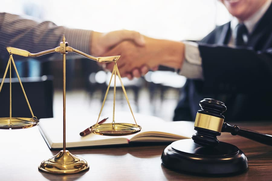 Handshake between a client and a private criminal defense attorney