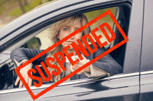 woman in car with drivers license suspension with suspended red stamp